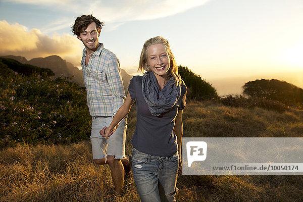 Junges Paar  das Hand in Hand in einer abgelegenen Landschaft geht
