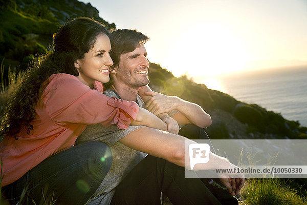 Südafrika  Paar mit Blick auf die Küste bei Sonnenuntergang