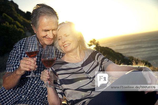 Südafrika  glückliches Seniorenpaar mit Gläsern Rotwein