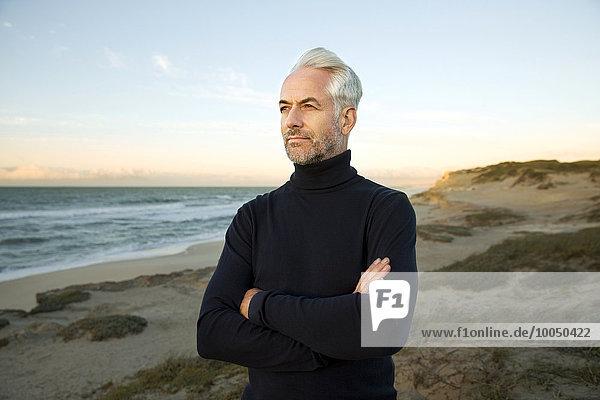 Südafrika  Porträt eines weißhaarigen Mannes mit Rollkragenpulli  der vor Sonnenaufgang auf den Dünen steht.