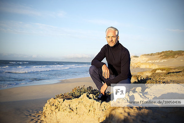Südafrika  Mann kauert auf Felsen am Strand vor Sonnenaufgang