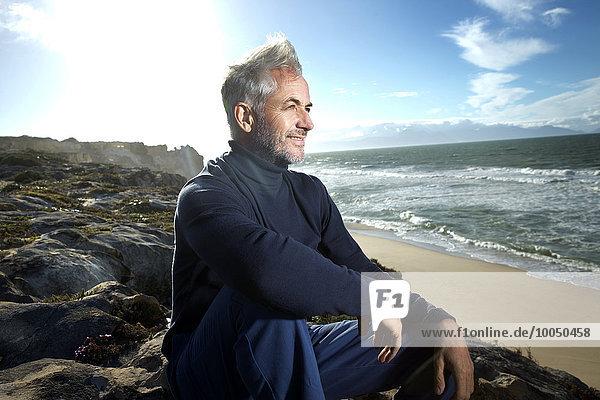 Südafrika  Porträt eines lächelnden Mannes auf Felsen am Strand