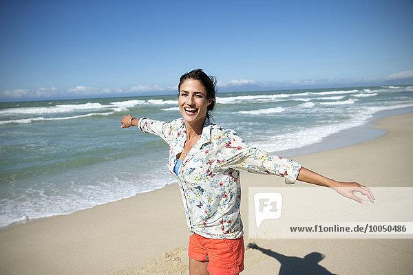 Südafrika  lachende Frau mit ausgestreckten Armen am Strand stehend