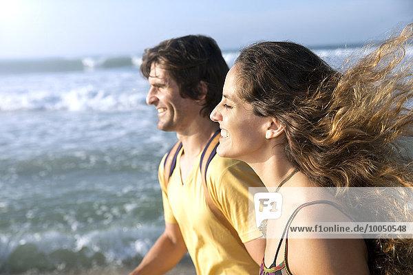 Südafrika  glückliches Paar  das am Strand spazieren geht