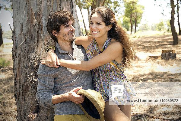 Südafrika  glückliches Paar vor einem Baumstamm