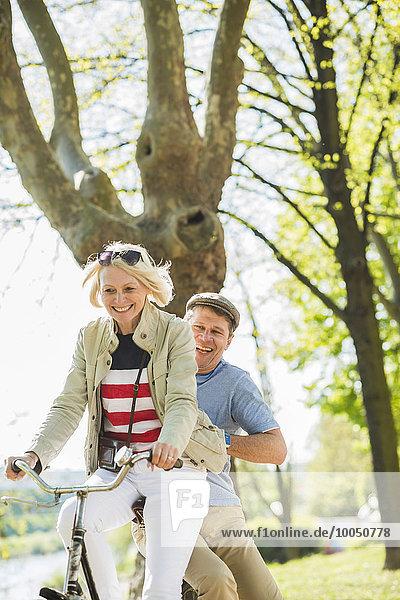 Ein reifes Paar im Park  ein Mann sitzt auf einem Gestell.