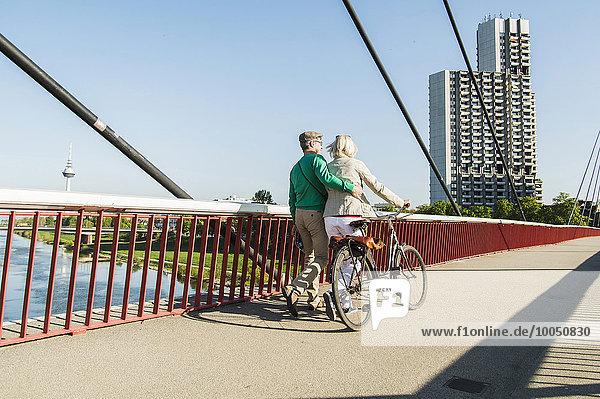 Deutschland  Mannheim  Altes Ehepaar überquert Brücke  Schiebefahrrad