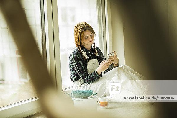 Junge Frau macht Pause vom Renovieren