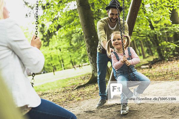 Glückliches Mädchen mit Vater und Mutter auf dem Spielplatz