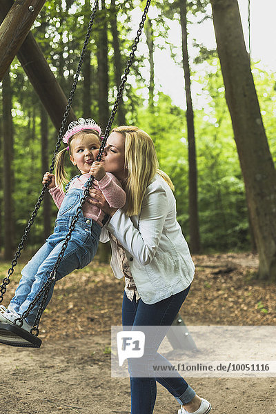 Mutter hält glückliche Tochter auf Schaukel