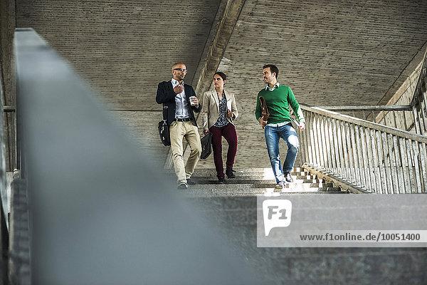 Drei Geschäftsleute diskutieren auf der Treppe