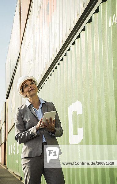 Geschäftsfrau mit digitalem Tablett und Schutzhelm im Containerhafen