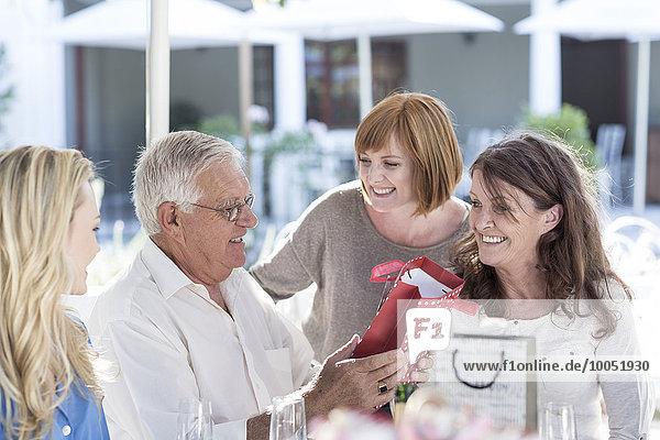 Three generations family celebrating grandfather's birthday at restaurant