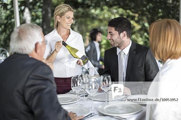 Kellnerin zeigt den Gästen Weißwein am Tisch