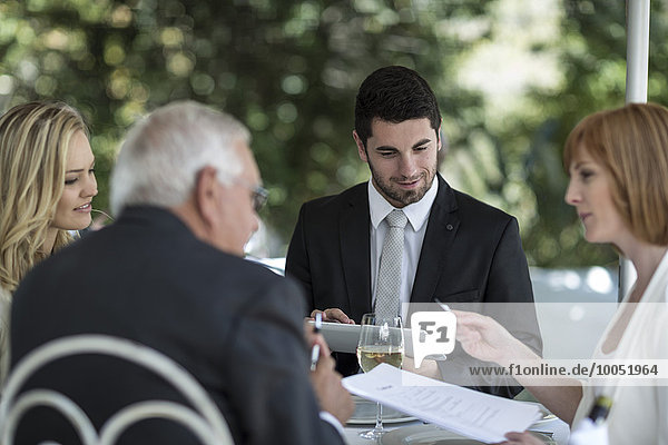 Elegante Leute im Außenrestaurant bei einem Gespräch