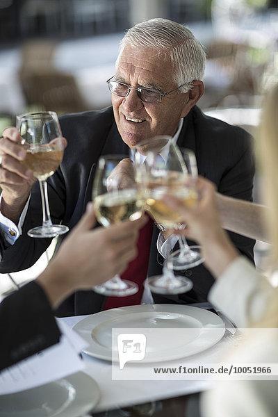 Leute im Außenrestaurant klirren an Weißweingläsern.