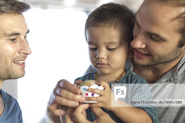 Schwules Paar backt Kuchen mit Sohn