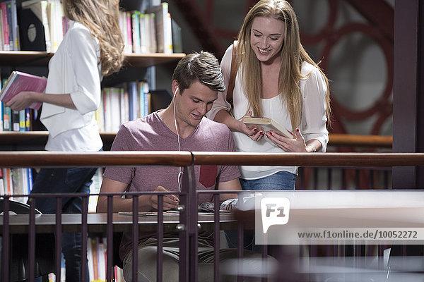 Drei Studenten in einer Bibliothek