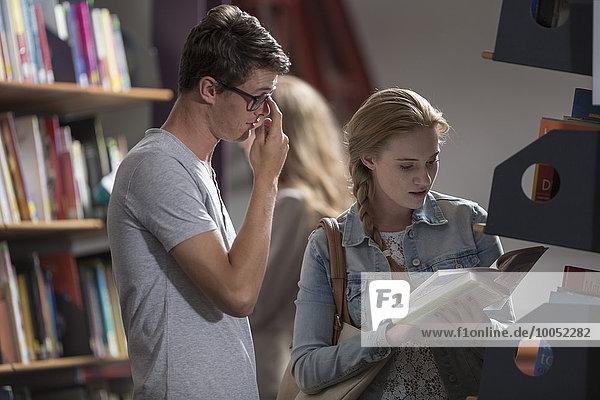 Studenten mit Buch in einer Bibliothek