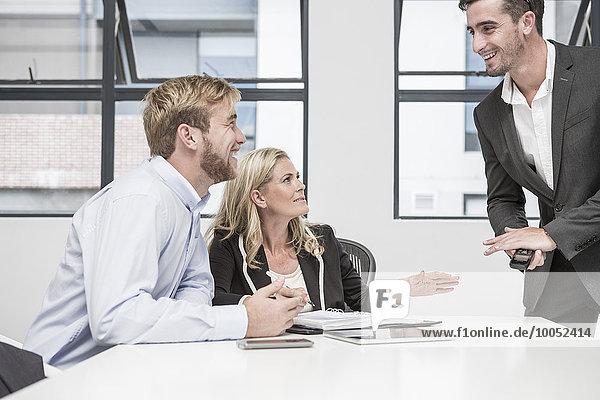 Drei lächelnde Geschäftsleute bei einem Büromeeting