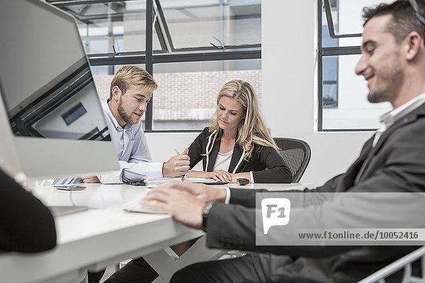Drei Geschäftsleute  die im Besprechungsraum arbeiten