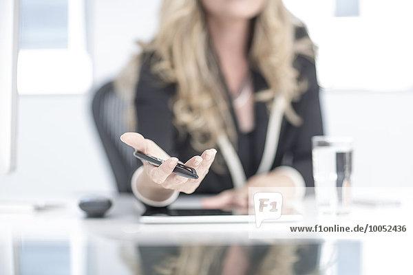 Geschäftsfrau im Büro mit Kugelschreiber in der Hand  Mittelteil