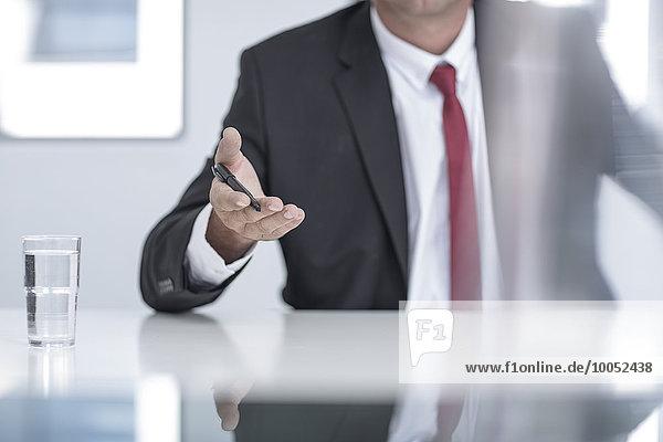 Geschäftsmann im Büro mit Kugelschreiber in der Hand  Mittelteil