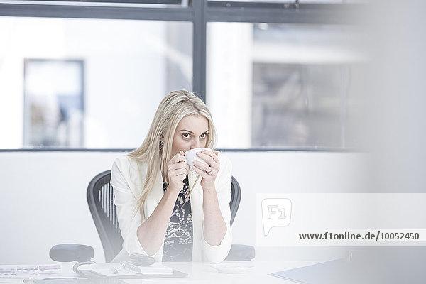 Geschäftsfrau beim Kaffeetrinken am Schreibtisch