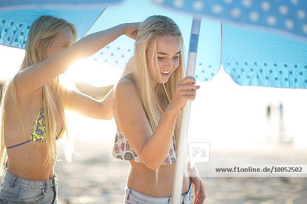 Zwei glückliche junge Frauen unter dem Sonnenschirm