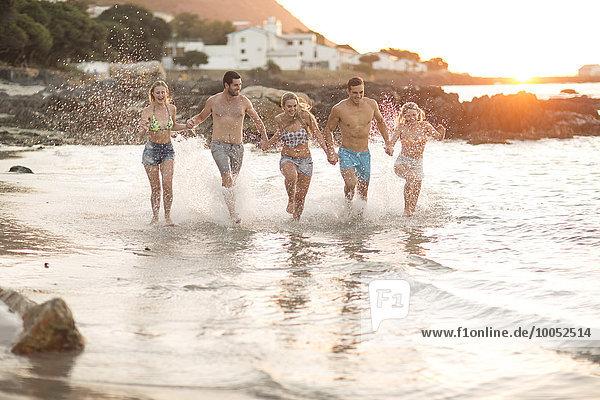 Fünf Freunde  die in Wellen am Strand rennen.