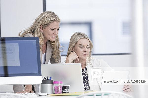 Zwei Geschäftsfrauen im Büro mit Laptop und digitalem Tablett