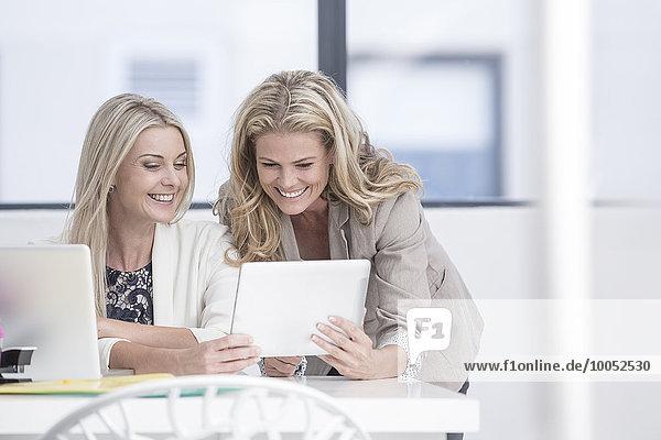 Zwei glückliche Geschäftsfrauen im Büro beim Betrachten des digitalen Tabletts