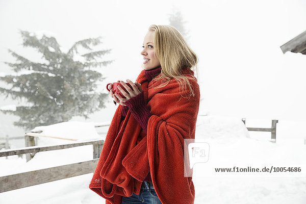 Young woman in snowy mist wrapped in red blanket drinking coffee