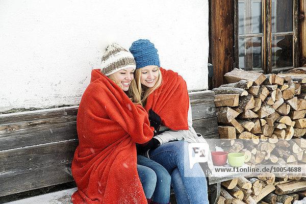 Zwei junge Freundinnen in rote Decke gehüllt  sitzen vor einer Holzhütte.