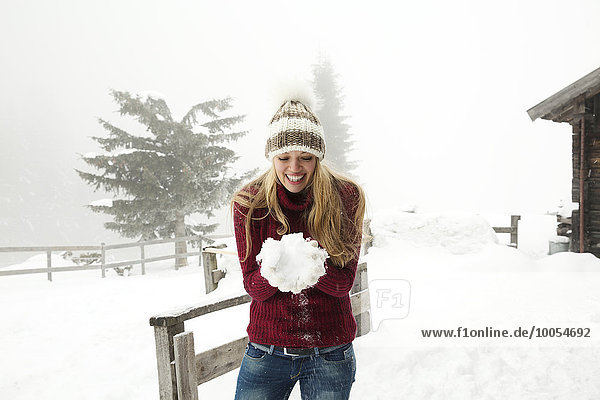 Young woman making a snowball