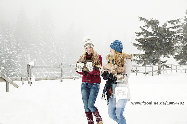 Two young female friends carrying logs in snow