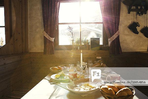 Sunlit breakfast table in log cabin