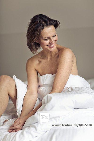 hoch oben sitzend Frau Bett Verpackung reifer Erwachsene reife Erwachsene Bettwäsche umwickelt
