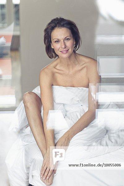 hoch oben sitzend Portrait Frau Bett Verpackung reifer Erwachsene reife Erwachsene Bettlaken Tuch umwickelt