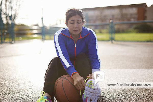 Reife Basketballspielerin beim Binden von Schnürsenkeln