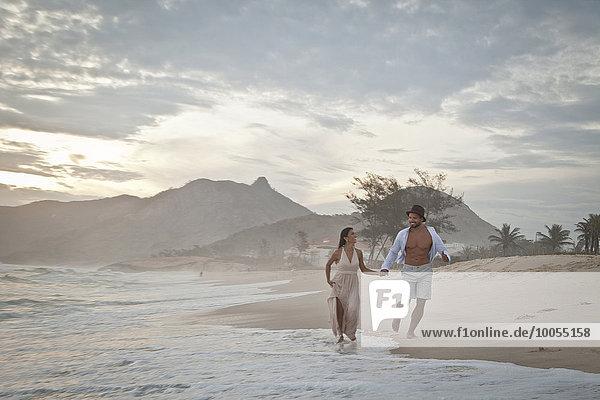Mittleres erwachsenes Paar läuft am Strand entlang  Hand in Hand