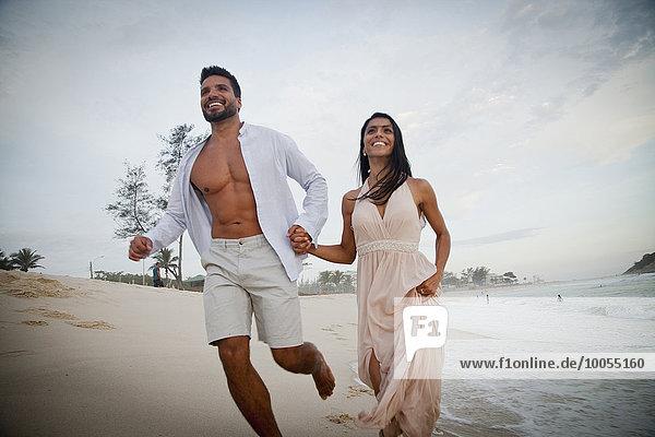 Mittleres erwachsenes Paar  das am Strand entlang läuft  Hand in Hand  Blickwinkel niedrig
