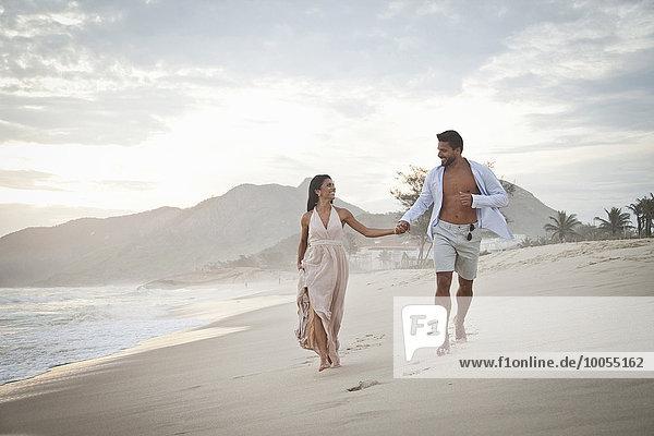 Mittleres erwachsenes Paar  das am Strand entlanggeht  Hand in Hand