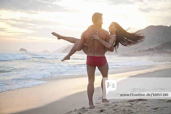 Mittleres erwachsenes Paar am Strand  Mann mit Frau im Arm  Rückansicht