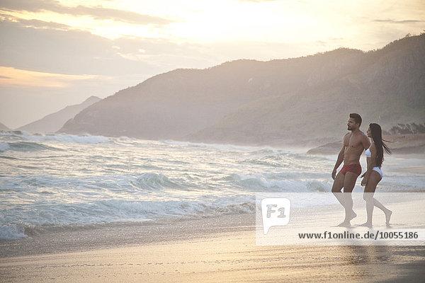 Mittleres erwachsenes Paar am Strand  in Badebekleidung  auf dem Weg zum Meer.