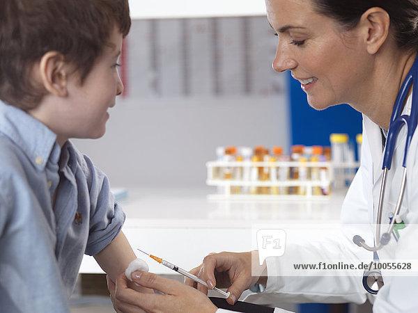 Arzt tröstender kleiner Junge in der Klinik