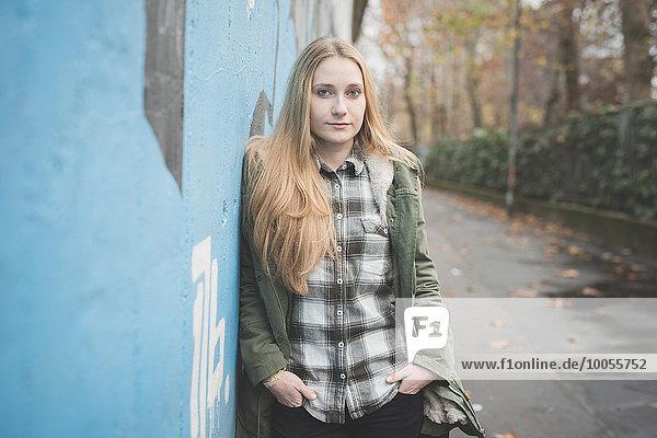 Junge Frau lehnt an Graffiti-Wand