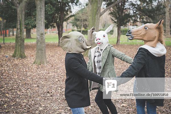 Drei Schwestern mit Tiermasken tanzen im Park