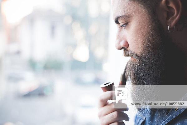 Junger bärtiger Mann raucht Pfeife am Fenster