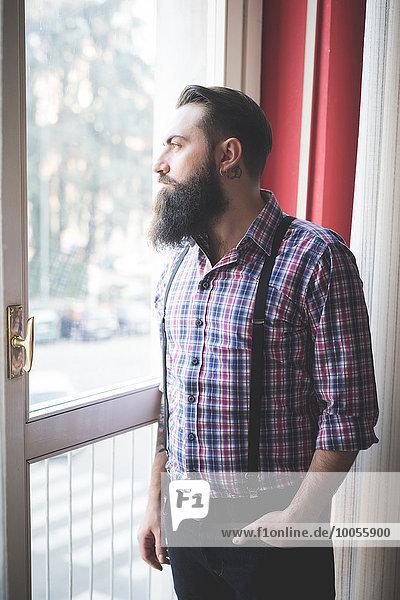 Junger bärtiger Mann in Hosenträgern  der aus der Tür schaut.